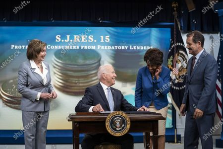 """United States President Joe Biden signs S.J.Res.15, one of the three Congressional Review Act bills, into law in Washington, DC,.The bills aim to reverse Trump era policies related to worker discrimination, methane emissions and the 'True Lender' rule. From left to right: Speaker of the US House of Representatives Nancy Pelosi (Democrat of California), President Biden, US Representative Maxine Waters (Democrat of California) and US Representative Jesus """"Chuy"""" Garcia (Democrat of Illinois)."""