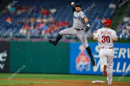 Miami Marlins shortstop Miguel Rojas leaps after getting the force out on Philadelphia Phillies' Luke Williams, right, during the eighth inning of a baseball game, in Philadelphia. The Marlins won 11-6