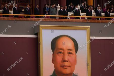 Chinese President Xi Jinping, center, stands above a large portrait of the late leader Mao Zedong during a ceremony to mark the 100th anniversary of the founding of the ruling Chinese Communist Party at Tiananmen Gate in Beijing
