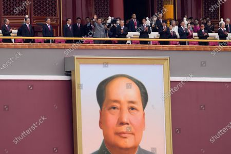 Stock Photo of Chinese President Xi Jinping, center, waves above a large portrait of the late leader Mao Zedong during a ceremony to mark the 100th anniversary of the founding of the ruling Chinese Communist Party at Tiananmen Gate in Beijing