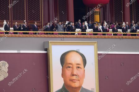 Stock Picture of Chinese President Xi Jinping, center, waves above a large portrait of the late leader Mao Zedong during a ceremony to mark the 100th anniversary of the founding of the ruling Chinese Communist Party at Tiananmen Gate in Beijing