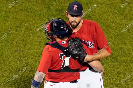 Boston Red Sox closer Matt Barnes hugs catcher Christian Vazquez (7) as they celebrate a 6-2 victory over the Kansas City Royals in a baseball game at Fenway Park early, in Boston