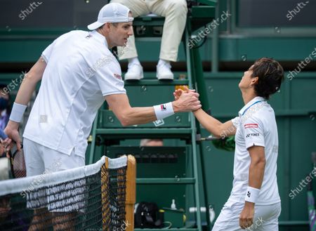 Yoshihito Nishioka (JPN) shakes hands with John Isner (USA) after his win in the first round of the Gentlemen's Singles on Court 18 at The Championships 2021