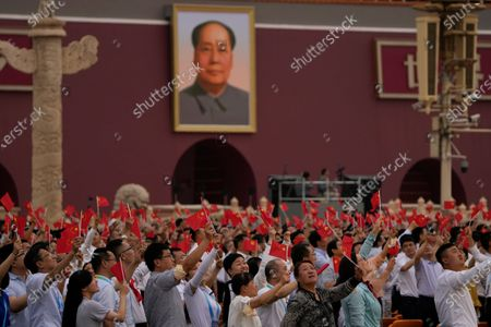People wave Chinese flags beneath a large portrait of the late leader Mao Zedong during a ceremony to mark the 100th anniversary of the founding of the ruling Chinese Communist Party at Tiananmen Gate in Beijing