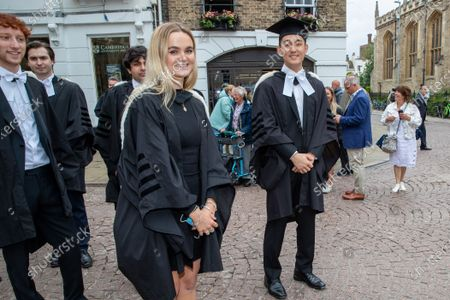 Stock Image of Students from St John's College Cambridge on their graduation day which has returned after the ceremony was cancelled last year due to the Coronavirus pandemic.Students dressed in black gowns as the traditional Cambridge University graduation ceremonies took place - after they were cancelled last year due to the Coronavirus pandemic.The students paraded into historic Senate House to collect their degrees from the prestigious university.Family and friends would normally watch the ceremony inside the Senate House, but this year they had to wait outside due to Covid restrictions. The ceremony was streamed online so guests could watch it over the Internet. Afterwards they were able to join the students for a picnic in the colleges' grounds.This year there were less students at the ceremonies, with some self-isolating and others choosing to attend extra ceremonies later in the year.Many parts of the degree ceremonies have their origin amongst the earliest customs of the university 800 years ago.Undergraduates are required to wear the gown of their college and the hood of the degree they are about to receive.Graduates are presented in the Senate House college by college, in order of foundation or recognition by the university, except for the royal colleges.Mortarboards are optional for Cambridge graduates and if worn they must carry them into the Senate House.
