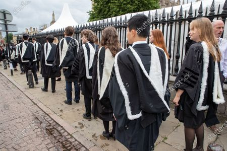 Stock Photo of Students from St John's College Cambridge on their graduation day which has returned after the ceremony was cancelled last year due to the Coronavirus pandemic.Students dressed in black gowns as the traditional Cambridge University graduation ceremonies took place - after they were cancelled last year due to the Coronavirus pandemic.The students paraded into historic Senate House to collect their degrees from the prestigious university.Family and friends would normally watch the ceremony inside the Senate House, but this year they had to wait outside due to Covid restrictions. The ceremony was streamed online so guests could watch it over the Internet. Afterwards they were able to join the students for a picnic in the colleges' grounds.This year there were less students at the ceremonies, with some self-isolating and others choosing to attend extra ceremonies later in the year.Many parts of the degree ceremonies have their origin amongst the earliest customs of the university 800 years ago.Undergraduates are required to wear the gown of their college and the hood of the degree they are about to receive.Graduates are presented in the Senate House college by college, in order of foundation or recognition by the university, except for the royal colleges.Mortarboards are optional for Cambridge graduates and if worn they must carry them into the Senate House.