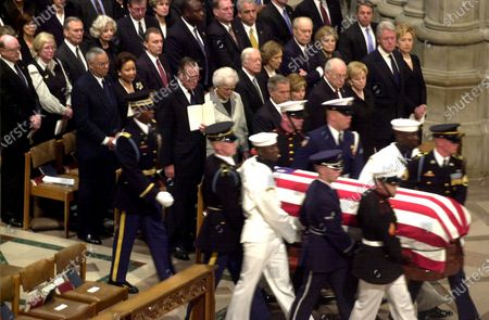 Stock Picture of A military honor guard carried the coffin bearing the body of former United States President Ronald Reagan past all of the living former Presidents and President George W. Bush. In the front row, from left to right: US President George W. Bush, Laura Bush, Vice President Dick Cheney, Lynne Cheney, former US President Bill Clinton and US Senator Hillary Clinton (Democrat of New York). In the second row are: former US President George H.W. Bush, Barbara Bush, former US President Jimmy Carter, Roslyn Carter, former US President Gerald Ford, Betty Ford, and an unidentified security person. US Secretary of State Colin Powell and his wife, Alma, are in the third row. US Secretary of the Treasury John W. Snow, Carolyn Snow, US Secretary of Defense Donald Rumsfeld, Joyce Rumsfeld, Attorney General John Ashcroft, and Janet Ashcroft. (RESTRICTION: NO New York or New Jersey Newspapers or newspapers within a 75 mile radius of New York City)