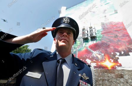 United States Air Force Colonel Keith Derbenwick, Senior Defense Attache of US embassy in Bucharest, salutes Lieutenant-General Ion Dobran (not pictured), 102, former fighter pilot in the Romanian Army in WWII, who arrives for the inauguration ceremony of the mural 'Icarus Metamorphosis' by Romanian artist Obie Platon, realised in honor of Dobran, in Bucharest, Romania, 01 July 2021. The mural, painted on a wall of a hotel, was designed in honor of veteran Ion Dobran, the last surviving WWII fighter pilot, and it symbolizes the air battle of June 06, 1944. In that air battle, US pilot Barrie Davis, a dogfight expert at the helm of a Mustang P51 war plane, was shot down by Romanian lieutenant Ion Dobran, who was flying a Messerschmitt Bf-109 fighter plane. Barrie Davis escaped with his life due to the way Dobran chose to attack, and thanked him for his gesture 66 years later, when the two fighters met at the Aviation Museum in Bucharest. Barry Davis died on August 19, 2014, at the age of 90. The mural depicts the two pilots that are symbolized by two Icarus characters, fighting in the air.