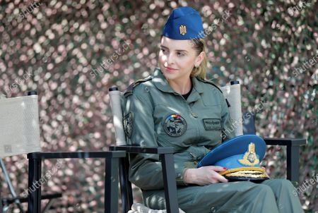 Romanian aviation lieutenant  Claudia Pop holds the military cap of Lieutenant-General Ion Dobran (not pictured), 102, former fighter pilot in the Romanian Army in WWII, during the inauguration ceremony of the mural 'Icarus Metamorphosis' by Romanian artist Obie Platon, realised in honor of Dobran, in Bucharest, Romania, 01 July 2021. The mural, painted on a wall of a hotel, was designed in honor of veteran Ion Dobran, the last surviving WWII fighter pilot, and it symbolizes the air battle of June 06, 1944. In that air battle, US pilot Barrie Davis, a dogfight expert at the helm of a Mustang P51 war plane, was shot down by Romanian lieutenant Ion Dobran, who was flying a Messerschmitt Bf-109 fighter plane. Barrie Davis escaped with his life due to the way Dobran chose to attack, and thanked him for his gesture 66 years later, when the two fighters met at the Aviation Museum in Bucharest. Barry Davis died on August 19, 2014, at the age of 90. The mural depicts the two pilots that are symbolized by two Icarus characters, fighting in the air.