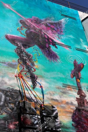 Stock Image of A view of the mural 'Icarus Metamorphosis' by Romanian artist Obie Platon, realised in honor of Lieutenant-General Ion Dobran (not pictured), 102, former fighter pilot in the Romanian Army in WWII, taken during the inauguration ceremony in Bucharest, Romania, 01 July 2021. The mural, painted on a wall of a hotel, was designed in honor of veteran Ion Dobran, the last surviving WWII fighter pilot, and it symbolizes the air battle of June 06, 1944. In that air battle, US pilot Barrie Davis, a dogfight expert at the helm of a Mustang P51 war plane, was shot down by Romanian lieutenant Ion Dobran, who was flying a Messerschmitt Bf-109 fighter plane. Barrie Davis escaped with his life due to the way Dobran chose to attack, and thanked him for his gesture 66 years later, when the two fighters met at the Aviation Museum in Bucharest. Barry Davis died on August 19, 2014, at the age of 90. The mural depicts the two pilots that are symbolized by two Icarus characters, fighting in the air.