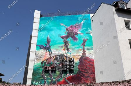 Stock Picture of A view of the mural 'Icarus Metamorphosis' by Romanian artist Obie Platon, realised in honor of Lieutenant-General Ion Dobran (not pictured), 102, former fighter pilot in the Romanian Army in WWII, taken during the inauguration ceremony in Bucharest, Romania, 01 July 2021. The mural, painted on a wall of a hotel, was designed in honor of veteran Ion Dobran, the last surviving WWII fighter pilot, and it symbolizes the air battle of June 06, 1944. In that air battle, US pilot Barrie Davis, a dogfight expert at the helm of a Mustang P51 war plane, was shot down by Romanian lieutenant Ion Dobran, who was flying a Messerschmitt Bf-109 fighter plane. Barrie Davis escaped with his life due to the way Dobran chose to attack, and thanked him for his gesture 66 years later, when the two fighters met at the Aviation Museum in Bucharest. Barry Davis died on August 19, 2014, at the age of 90. The mural depicts the two pilots that are symbolized by two Icarus characters, fighting in the air.
