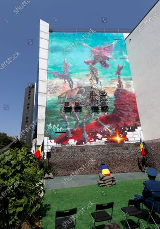 A view of the mural 'Icarus Metamorphosis' by Romanian artist Obie Platon, realised in honor of Lieutenant-General Ion Dobran (not pictured), 102, former fighter pilot in the Romanian Army in WWII, taken during the inauguration ceremony in Bucharest, Romania, 01 July 2021. The mural, painted on a wall of a hotel, was designed in honor of veteran Ion Dobran, the last surviving WWII fighter pilot, and it symbolizes the air battle of June 06, 1944. In that air battle, US pilot Barrie Davis, a dogfight expert at the helm of a Mustang P51 war plane, was shot down by Romanian lieutenant Ion Dobran, who was flying a Messerschmitt Bf-109 fighter plane. Barrie Davis escaped with his life due to the way Dobran chose to attack, and thanked him for his gesture 66 years later, when the two fighters met at the Aviation Museum in Bucharest. Barry Davis died on August 19, 2014, at the age of 90. The mural depicts the two pilots that are symbolized by two Icarus characters, fighting in the air.