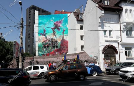 Stock Photo of A view of the mural 'Icarus Metamorphosis' by Romanian artist Obie Platon, realised in honor of Lieutenant-General Ion Dobran (not pictured), 102, former fighter pilot in the Romanian Army in WWII, taken during the inauguration ceremony in Bucharest, Romania, 01 July 2021. The mural, painted on a wall of a hotel, was designed in honor of veteran Ion Dobran, the last surviving WWII fighter pilot, and it symbolizes the air battle of June 06, 1944. In that air battle, US pilot Barrie Davis, a dogfight expert at the helm of a Mustang P51 war plane, was shot down by Romanian lieutenant Ion Dobran, who was flying a Messerschmitt Bf-109 fighter plane. Barrie Davis escaped with his life due to the way Dobran chose to attack, and thanked him for his gesture 66 years later, when the two fighters met at the Aviation Museum in Bucharest. Barry Davis died on August 19, 2014, at the age of 90. The mural depicts the two pilots that are symbolized by two Icarus characters, fighting in the air.