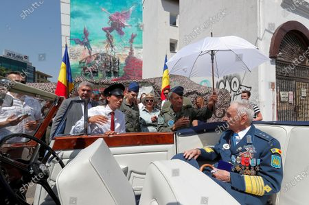 Lieutenant-General Ion Dobran (R), 102, former fighter pilot in the Romanian Army in WWII prepares for leaving in a 1947 Rolls-Royce Silver Wraith limousine, after the inauguration ceremony of the mural 'Icarus Metamorphosis' by Romanian artist Obie Platon, realised in honor of Dobran in Bucharest, Romania, 01 July 2021. The mural, painted on a wall of a hotel, was designed in honor of veteran Ion Dobran, the last surviving WWII fighter pilot, and it symbolizes the air battle of June 06, 1944. In that air battle, US pilot Barrie Davis, a dogfight expert at the helm of a Mustang P51 war plane, was shot down by Romanian lieutenant Ion Dobran, who was flying a Messerschmitt Bf-109 fighter plane. Barrie Davis escaped with his life due to the way Dobran chose to attack, and thanked him for his gesture 66 years later, when the two fighters met at the Aviation Museum in Bucharest. Barry Davis died on August 19, 2014, at the age of 90. The mural depicts the two pilots that are symbolized by two Icarus characters, fighting in the air.