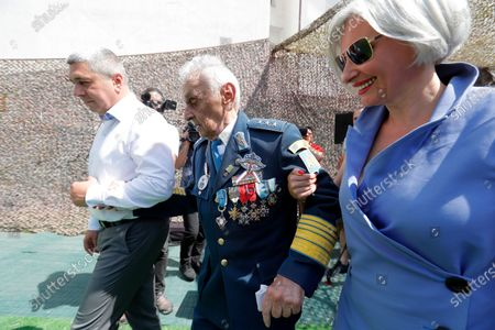 Lieutenant-General Ion Dobran (C), 102, former fighter pilot in the Romanian Army in WWII leaves after the inauguration ceremony of the mural 'Icarus Metamorphosis' by Romanian artist Obie Platon, realised in honor of Dobran in Bucharest, Romania, 01 July 2021. The mural, painted on a wall of a hotel, was designed in honor of veteran Ion Dobran, the last surviving WWII fighter pilot, and it symbolizes the air battle of June 06, 1944. In that air battle, US pilot Barrie Davis, a dogfight expert at the helm of a Mustang P51 war plane, was shot down by Romanian lieutenant Ion Dobran, who was flying a Messerschmitt Bf-109 fighter plane. Barrie Davis escaped with his life due to the way Dobran chose to attack, and thanked him for his gesture 66 years later, when the two fighters met at the Aviation Museum in Bucharest. Barry Davis died on August 19, 2014, at the age of 90. The mural depicts the two pilots that are symbolized by two Icarus characters, fighting in the air.