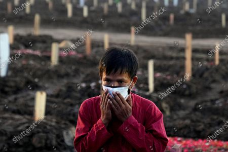 Man prays after the burial of a relative at Rorotan Cemetery, which is reserved for those who died of COVID-19, in Jakarta, Indonesia, . Indonesian President Joko Widodo announced new community restrictions and the mobilization of the National Police and other resources as the world's fourth-most populous country has seen a rapid surge in COVID-19 cases in the last two weeks