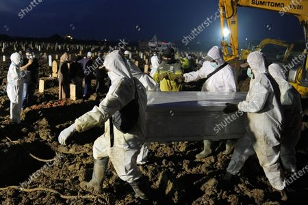 Workers carry a coffin containing the body of a COVID-19 victim during a burial at Rorotan Cemetery in Jakarta, Indonesia, . Indonesian President Joko Widodo announced new community restrictions and the mobilization of the National Police and other resources as the world's fourth-most populous country has seen a rapid surge in COVID-19 cases in the last two weeks