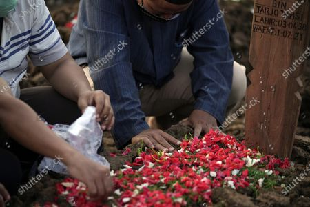 Man prays at the grave of a relative after his burial at Rorotan Cemetery, which is reserved for those who died of COVID-19, in Jakarta, Indonesia, . Indonesian President Joko Widodo announced new community restrictions and the mobilization of the National Police and other resources as the world's fourth-most populous country has seen a rapid surge in COVID-19 cases in the last two weeks