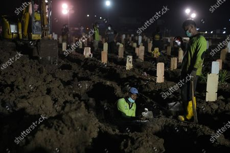Workers prepare new graves at Rorotan Cemetery, which is reserved for those who died of COVID-19, in Jakarta, Indonesia, . Indonesian President Joko Widodo announced new community restrictions and the mobilization of the National Police and other resources as the world's fourth-most populous country has seen a rapid surge in COVID-19 cases in the last two weeks