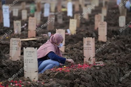 Woman sits at the grave of a relative who died of COVID-19 after her burial at Rorotan Cemetery in Jakarta, Indonesia, . Indonesian President Joko Widodo announced new community restrictions and the mobilization of the National Police and other resources as the world's fourth-most populous country has seen a rapid surge in COVID-19 cases in the last two weeks