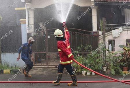 Fire fighters spray disinfectant in an attempt to curb the spread of coronavirus outbreak at a neighborhood in Tangerang on the outskirts of Jakarta, Indonesia,. Indonesian President Joko Widodo announced new community restrictions and the mobilization of the National Police and other resources as the world's fourth-most populous country has seen a rapid surge in COVID-19 cases in the last two weeks