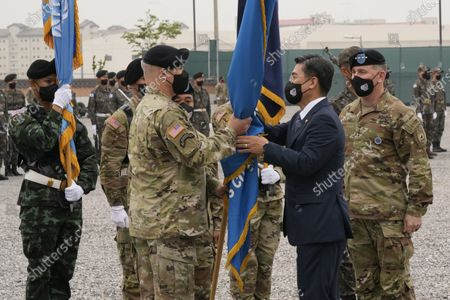 Incoming commander, Gen. Paul J. LaCamera, center left, receives the South Korea-U.S. Combined Forces Command flag from South Korean Defense Minister Suh Wook as outgoing commander, Gen. Robert B. Abrams, right, watches during a change-of-command ceremony for the United Nations Command, Combined Forces Command, and United States Forces Korea at Barker Field in Pyeongtaek, South Korea