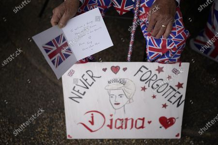Royal fan Terry Hutt, aged 86 waits to see the statue of Diana, Princess of Wales, a day after its unveiling, in the Sunken Garden at Kensington Palace, London, . The statue, which shows a larger-than-life Diana surrounded by three children, was commissioned by Prince William and Prince Harry in 2017
