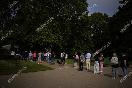 People queue up to see the statue of Diana, Princess of Wales, a day after its unveiling, in the Sunken Garden at Kensington Palace, London, . The statue, which shows a larger-than-life Diana surrounded by three children, was commissioned by Prince William and Prince Harry in 2017