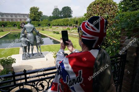 Members of the public view the statue of Diana, Princess of Wales, in the Sunken Garden at Kensington Palace, London.