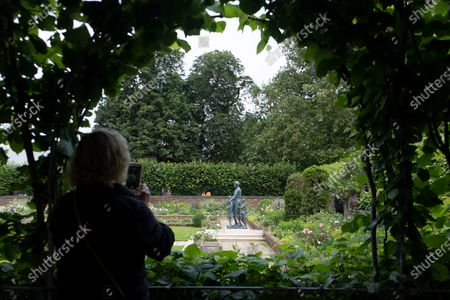 Members of the public view the statue of the late Princess Diana in the new landscaped Sunken Garden of Kensington Gardens.