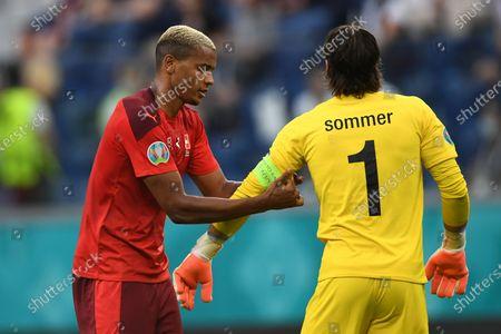 Switzerland's Manuel Akanji adjusts the caption armband to goalkeeper Yann Sommer during the Euro 2020 soccer championship quarterfinal match between Switzerland and Spain, at the Saint Petersburg stadium in Saint Petersburg