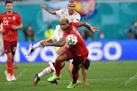 Switzerland's Manuel Akanji eyes the ball during the Euro 2020 soccer championship quarterfinal match between Switzerland and Spain, at the Saint Petersburg stadium in Saint Petersburg