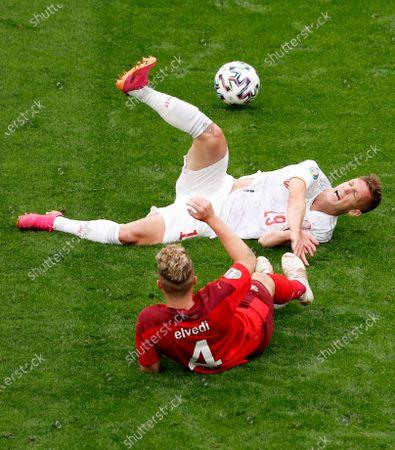 Switzerland's Nico Elvedi, down, collides with Spain's Dani Olmo during the Euro 2020 soccer championship quarterfinal match between Switzerland and Spain at Saint Petersburg Stadium in St. Petersburg, Russia