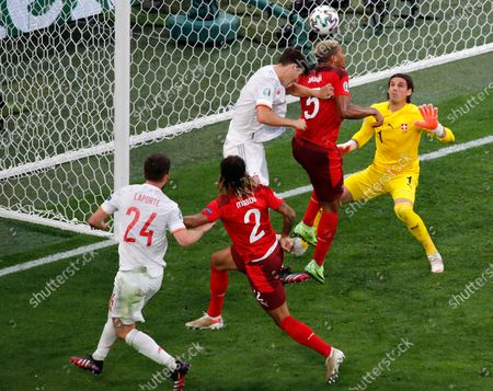 Switzerland's goalkeeper Yann Sommer, right, watches as Switzerland's Manuel Akanji, 2nd right, heads the ball during the Euro 2020 soccer championship quarterfinal match between Switzerland and Spain at Saint Petersburg Stadium in St. Petersburg, Russia