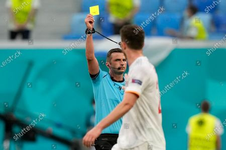 Referee Michael Oliver shows a yellow card to Spain's Aymeric Laporte during the Euro 2020 soccer championship quarterfinal match between Switzerland and Spain at Saint Petersburg stadium in St. Petersburg, Russia