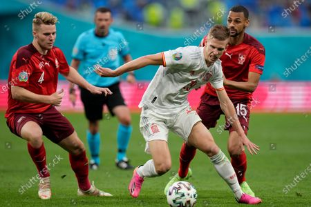 Spain's Dani Olmo controls the ball between Switzerland's Nico Elvedi, left, and Djibril Sow, right, during the Euro 2020 soccer championship quarterfinal match between Switzerland and Spain at Saint Petersburg stadium in St. Petersburg, Russia