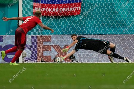 Spain's goalkeeper Unai Simon stops a penalty shot from Switzerland's Manuel Akanji, left, during a penalty shootout after extra time during the Euro 2020 soccer championship quarterfinal match between Switzerland and Spain at Saint Petersburg stadium in St. Petersburg, Russia