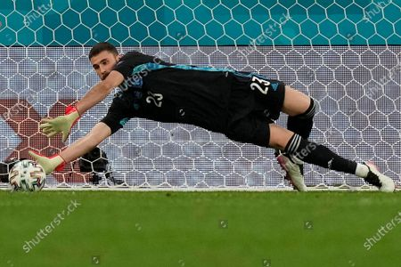 Spain's goalkeeper Unai Simon stops a penalty shot from Switzerland's Manuel Akanji during a penalty shootout after extra time during the Euro 2020 soccer championship quarterfinal match between Switzerland and Spain at Saint Petersburg stadium in St. Petersburg, Russia