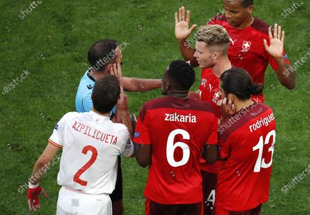 Stock Image of Players of Switzerland (red) argue with English referee Michael Oliver (back L) during the UEFA EURO 2020 quarter final match between Switzerland and Spain in St.Petersburg, Russia, 02 July 2021.
