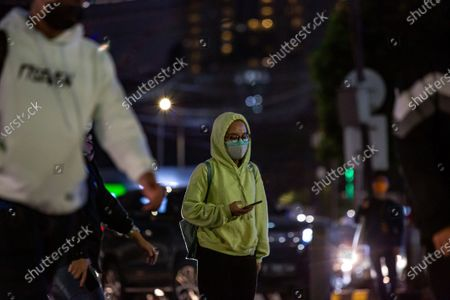 A women wear double protective face masks walk in business district on the last day before the emergency public activity restrictions (Emergency PPKM) in Jakarta, Indonesia on 2 July 2021. The Jakarta police would apply the emergency public activity restrictions (Emergency PPKM) beginning Saturday, July 3, 2021 following Indonesia's President Joko Widodo announced on Thursday to place 'emergency restrictions' on Java and Bali islands from July 3 to 21. All entry and exit points to and from Jakarta would be shut beginning 12 a.m. today. People are only allowed outside of their home for emergency and essential purposes. On Friday, Indonesia recorded 25,830 news COVID-19 cases in the past 24 hours, a fresh record of daily spike, bringing the total tally 2,228,938.