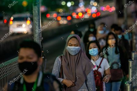 People wear protective face masks walk in business district on the last day before the emergency public activity restrictions (Emergency PPKM) in Jakarta, Indonesia on 2 July 2021. The Jakarta police would apply the emergency public activity restrictions (Emergency PPKM) beginning Saturday, July 3, 2021 following Indonesia's President Joko Widodo announced on Thursday to place 'emergency restrictions' on Java and Bali islands from July 3 to 21. All entry and exit points to and from Jakarta would be shut beginning 12 a.m. today. People are only allowed outside of their home for emergency and essential purposes. On Friday, Indonesia recorded 25,830 news COVID-19 cases in the past 24 hours, a fresh record of daily spike, bringing the total tally 2,228,938.