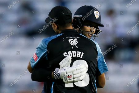 Stock Photo of Jade Dernbach of Derbyshire Falcons hugs Ish Sodhi of Worcestershire Rapids