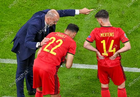 Belgium's manager Roberto Martinez, left, talks with substitutes Belgium's Nacer Chadli, and Dries Mertens, right, as they prepare to join the game during the Euro 2020 soccer championship quarterfinal match between Belgium and Italy at the Allianz Arena in Munich, Germany