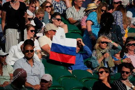 Spectator holding a Russian flag watches the during the men's singles third round match on between Russia's Daniil Medvedev and Croatia's Marin Cilic on day six of the Wimbledon Tennis Championships in London