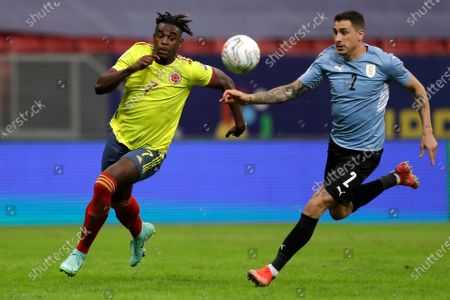 Uruguay's Jose Gimenez, right, and Colombia's Duvan Zapata battle for the ball during a Copa America quarterfinal soccer match at the National stadium in Brasilia, Brazil