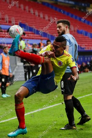 Stock Picture of Colombia's William Tesillo tries to control the ball challenged by Uruguay's Nahitan Nandez during a Copa America quarterfinal soccer match at the National stadium in Brasilia, Brazil