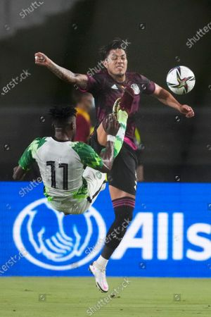 Nigeria forward Charles Atshimene (11) and Mexico midfielder Jonathan Dos Santos (6) kick the ball during the first half of an international friendly soccer match, in Los Angeles
