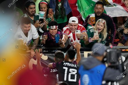 Fans greet Mexico midfielder Jonathan Dos Santos (6) and defender Efrain Alvarez (18) as they celebrate scoring a goal during the second half of an international friendly soccer match against Nigeria, in Los Angeles