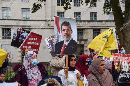 A protester holds a picture of the former president of Egypt, Mohamed Morsi, during the demonstration Protesters gathered outside Downing Street on the anniversary of the 2013 coup in Egypt.