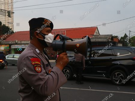 """Stock Picture of President Joko Widodo has officially issued a policy of """"Pemberlakuan Pembatasan Kegiatan Masyarakat"""" (PPKM) to reduce some public activities to prevent the spread of Covid-19 from spreading. The policy will apply from 3 July to 20 July, 2021, with a focus on being applied in Java to Bali. The situation in Depok, West Java, the police officers are turning some vehicles from passing through.Meanwhile the vehicles that are allowed to pass are ambulance and only for residents who have very important matters."""